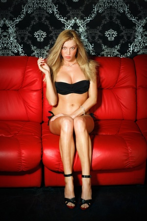 Bashful young blonde lady in black lingerie sitting on red leather sofa photo