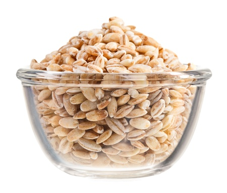 pearl barley: Pearl barley heap in small glass bowl, isolated on white Stock Photo