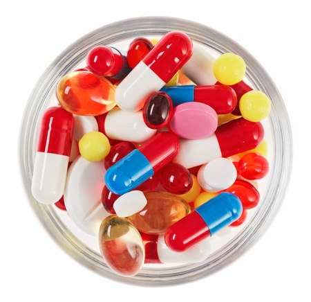Pills, tablets and drugs heap in glass bowl isolated on white photo