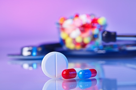 Pills and tablets macro still life on violet, medical therapeutic concept photo