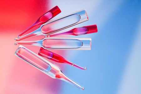 Medical ampoules on red and blue vivid color background photo