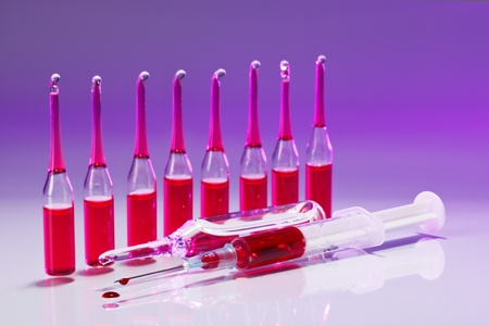 drop of blood: Red Ampoules and syringe still life in vivid colors