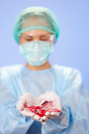 Doctor  woman  holding many medical ampoules in her hands photo