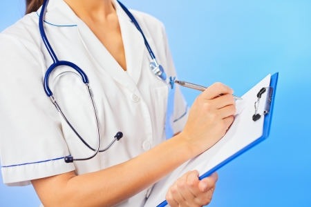 Doctor (woman) writing on clipboard, waist-high portrait on blue photo