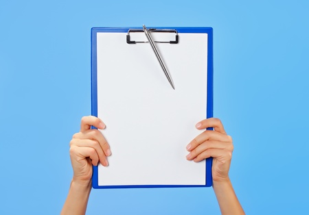 Clipboard in female hands on blue background Stock Photo - 13009615