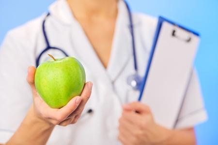 Doctor (woman) holding green apple with copy space on blue photo