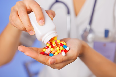 Pills, tablets and drugs pouring from bottle in doctors hand on blue background