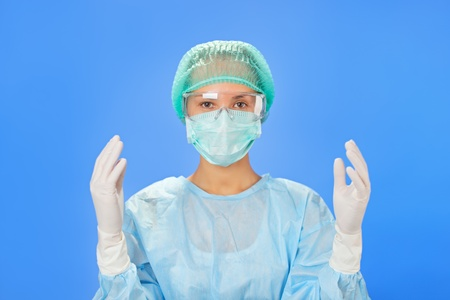 gloves nurse: Young beautiful surgeon doctor (woman) before operation on blue