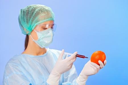 Young woman doctor injecting orange fruit with syringe on blue photo