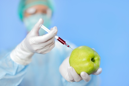 Young woman doctor injecting green apple with syringe on blue Stock Photo - 13009614
