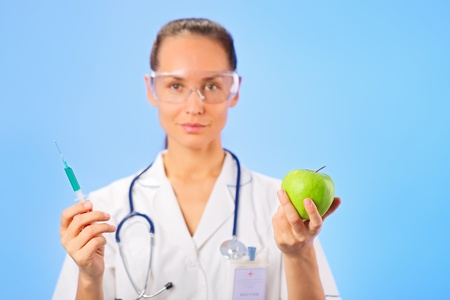 Young woman doctor injecting green apple with syringe on blue photo