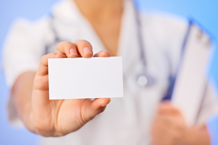 Doctor (woman) holding blank business card with copy space on blue