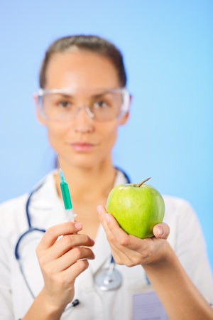 woman squirt: Young woman doctor injecting green apple with syringe on blue