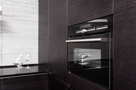 Part of black hardwood kitchen with build-in microwave oven photo