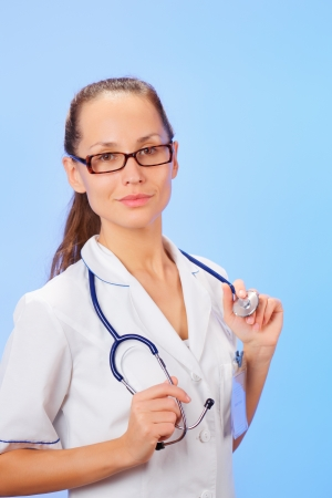 Therapeutic doctor (woman) waist-high portrait with stethoscope on blue photo