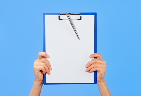 Clipboard in female hands on blue background photo