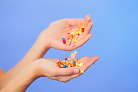 Pills, tablets and drugs pouring in doctors hands on blue background photo