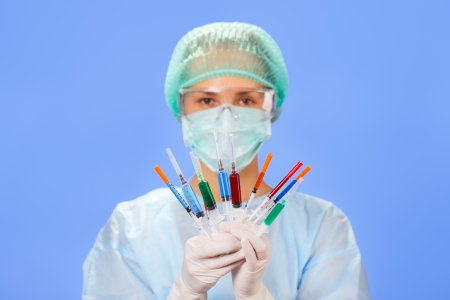 Young woman doctor with many multicolor syringes in hands on blue photo