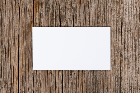 Empty white card over old textured wooden background photo