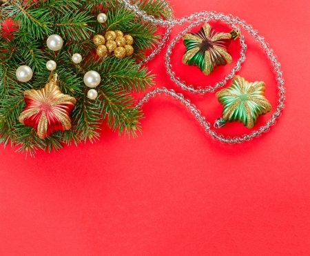 Christmas decorations and fir branch on red background photo