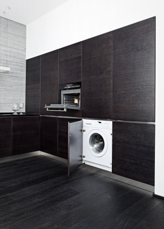Build-in washing machine and cooker on modern black kitchen photo