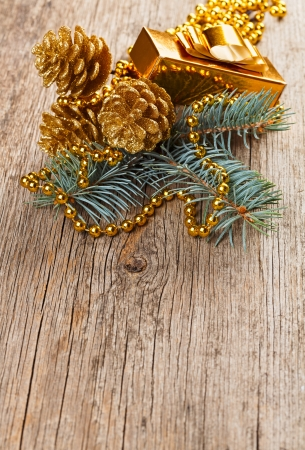 Christmas golden decorations on pine branch on wooden background photo