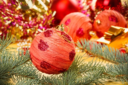 Red decoration ball with spruce branch on blurred  Christmas background photo