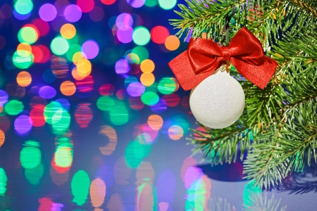 Christmas tree decoration ball with spruce branch on bokeh background photo