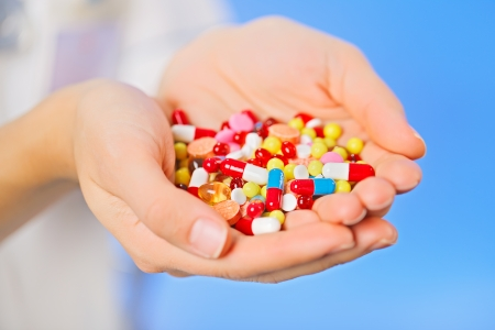 antibiotic pills: Pills, tablets and drugs heap in doctors hand on blue background Stock Photo