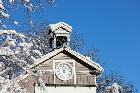 Old wooden snow covered chapel with clock photo