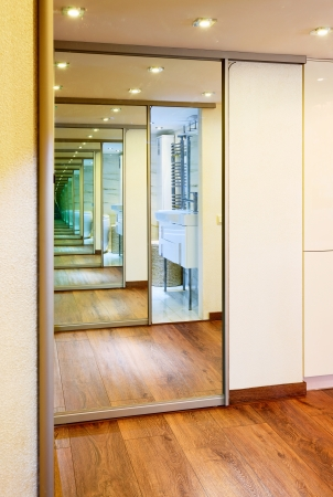 Sliding-door mirror wardrobe in modern hall interior with infinity reflections photo