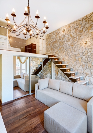 Modern style two-high living-room interior with staircase and stone wall photo