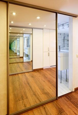 Sliding-door mirror wardrobe in modern hall interior with infinityreflections photo