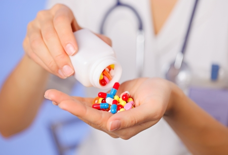 Pills, tablets and drugs pouring from bottle in doctors hand on blue background photo