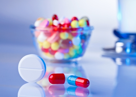 Pills and tablets macro still life on white blue, medical therapeutic concept photo