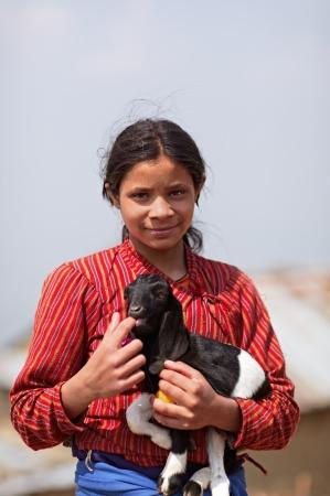 indigence: NAGARKOT, NEPAL - APRIL 5  Portrait of young unidentified Nepalese girl with a kid goat on April 5, 2009 in Nagarkot Village, Kathmandu, Central Region, Nepal  Editorial