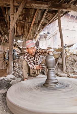 craft product: BHAKTAPUR, NEPAL - APRIL 5  Bhaktapur indigenous potter makes earthenware with turning wheel on April 5, 2009 in Bhaktapur, Nepal  Bhaktapur is listed as a World Heritage Site by UNESCO for its rich culture, temples, and wood, metal and stone artwork