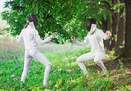 rapier: Two rapier fencer women fighting over beautiful nature park background Stock Photo