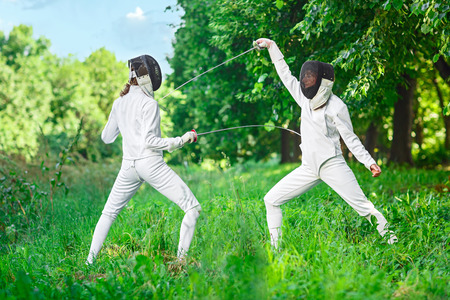 rapier: Two rapier fencer women fighting over beautiful nature background
