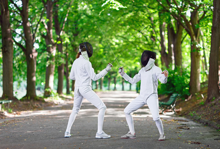 staying: Two rapier fencers women staying in park alley getting ready for competition