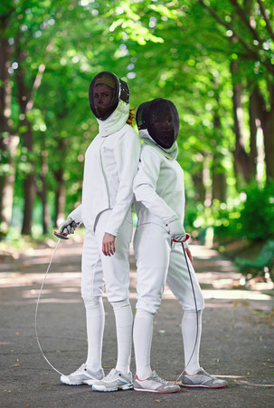 fencers: Two rapier fencers women staying in park alley getting ready for competition
