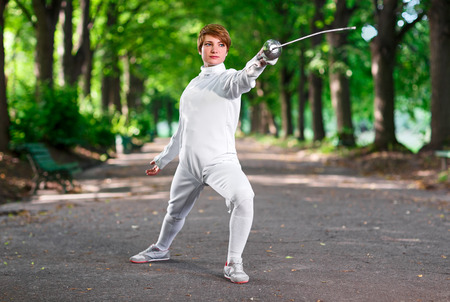 rapier: Young beautiful rapier fencer woman staying in park alley ready for competition Stock Photo