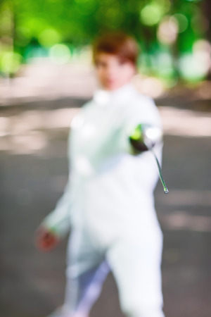 rapier: Tip of rapier held by fencer woman staying in park alley, shallow depth of field Stock Photo