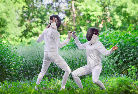 fencing sword: Two rapier fencer women fighting over beautiful nature park background Stock Photo