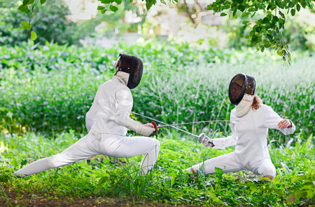 women fighting: Two rapier fencer women fighting over beautiful nature park background Stock Photo
