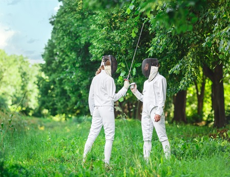 fencers: Two fencers women staying in park with crossed rapiers getting ready for competition