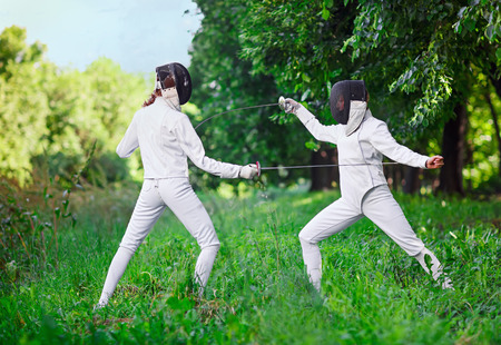 women fighting: Two rapier fencer women fighting over beautiful nature background