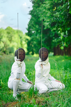 squatting down: Two fencers women squatting down with rapiers pointing up ready for competition