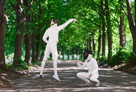 mujeres peleando: Dos mujeres fencer pinzas peleando por el callejón del parque, atacarse unos a otros en el salto