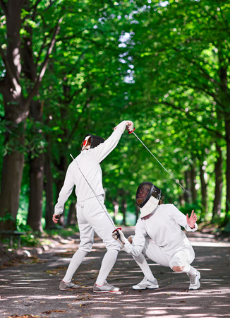 fencers: Two rapier fencers women fencing on park path
